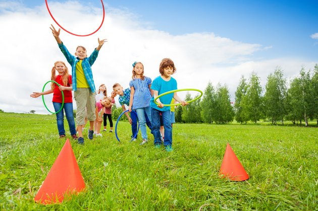 Happy children throw colorful hoops on cones