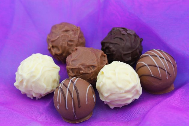 Assorted chocolates, pralines and truffles on purple background
