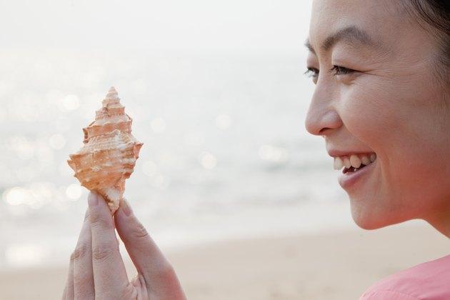 Young Woman Looking at Seashell