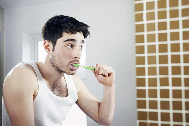 man brushing teeth in bathroom
