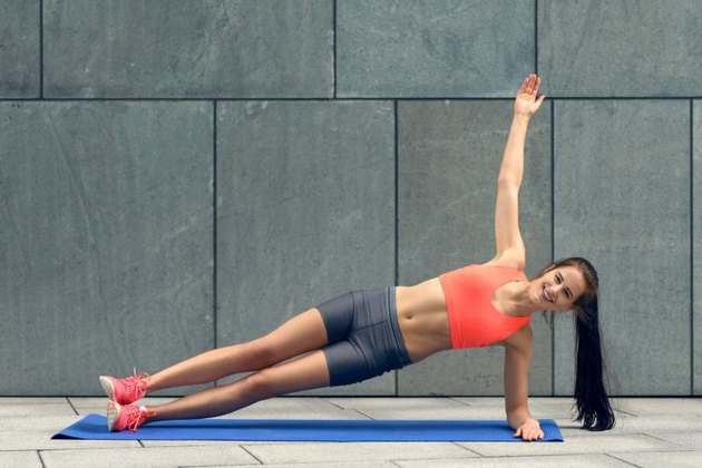 Fit young woman doing sideplanks, strengthening her core, working out on a mat, lifestyle and health concept