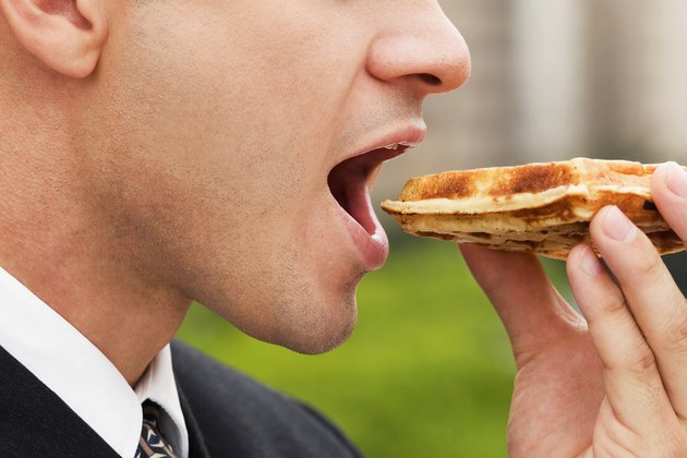 Close-up of a businessman eating a slice of pizza