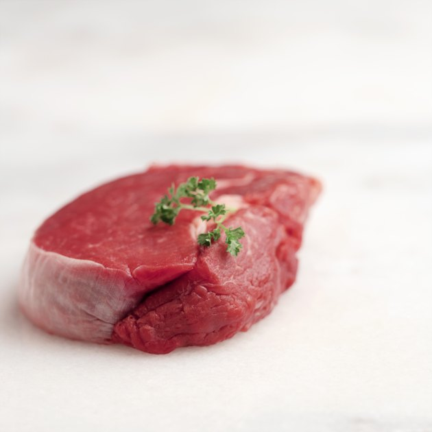Raw cut of red meat with parsley garnish