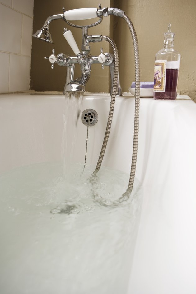 Bath with water flowing from faucet
