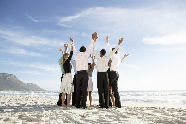 Group of people standing in circle on beach, arms raised