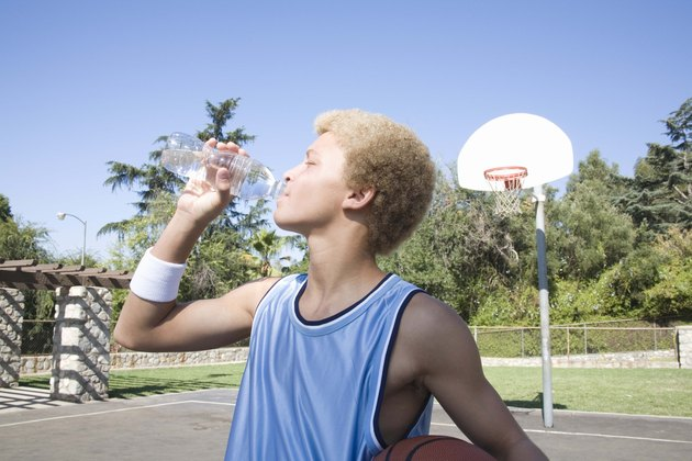 Teenage boy on basketball court drinking water bottle