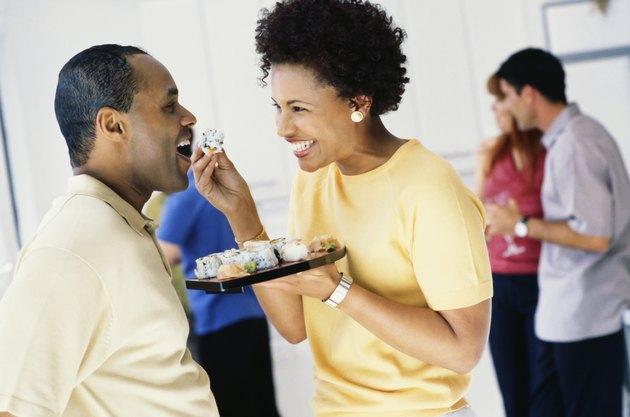 African woman feeding husband sushi