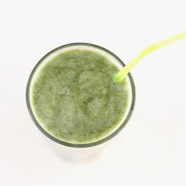 Elevated view of a glass of green juice with a straw