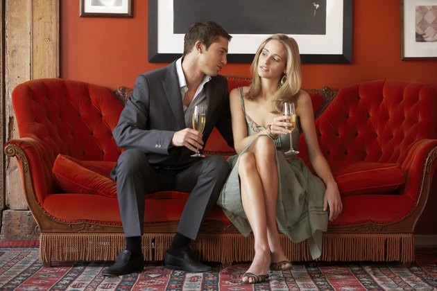 Young couple sitting on sofa holding champagne flutes