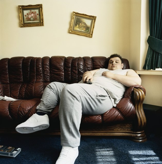 Overweight Young Man Falls Asleep While Lying on a Sofa Watching TV