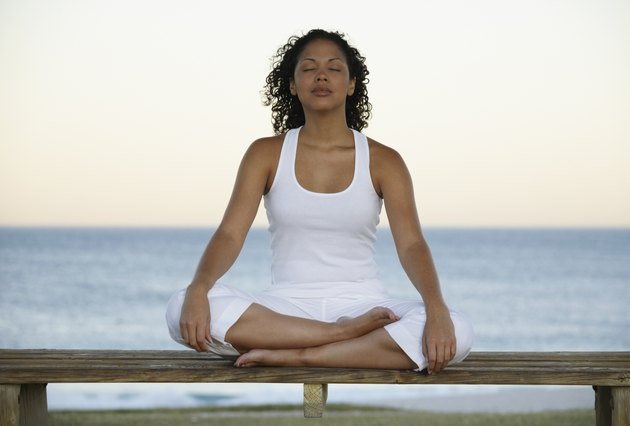 Mixed Race woman meditating near ocean