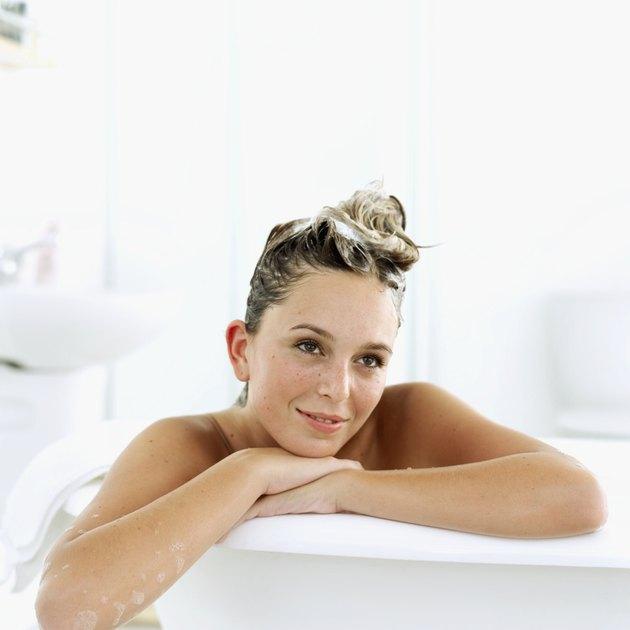 Portrait of a young woman sitting in a bathtub