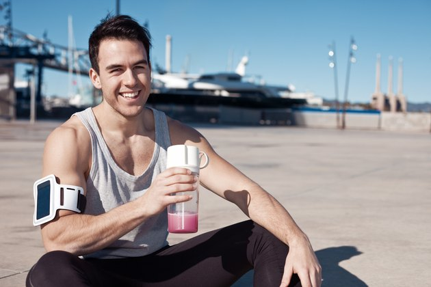 Smilingl athlete with protein cocktail