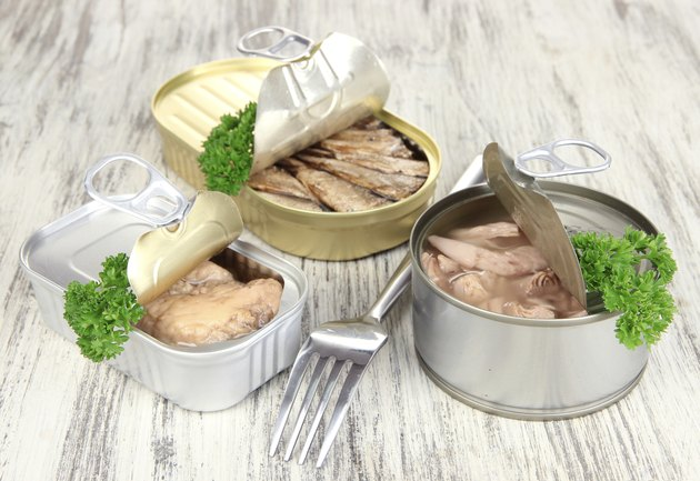 Open tin can, on wooden background