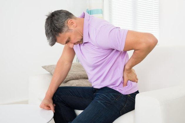 Mature Man Having Backache While Sitting On Sofa
