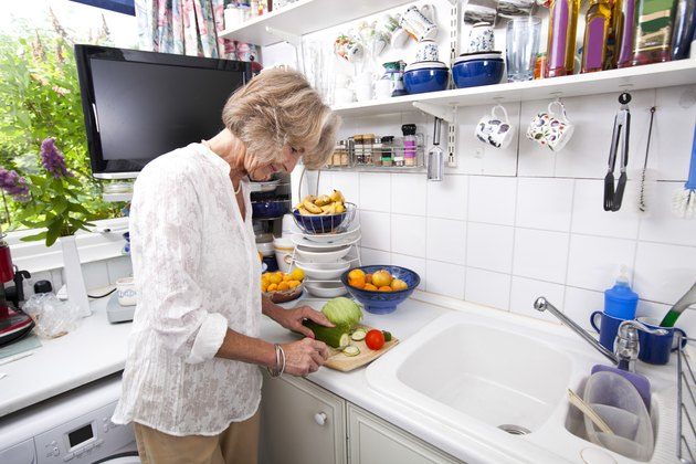 Senior woman chopping fresh vegetable while cooking at kitchen counter