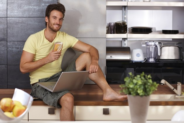Handsome man with laptop in kitchen