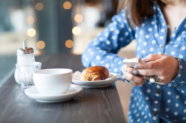 Midsection of woman using mobile phone with coffee and snack at cafe counter