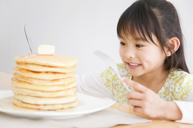 Girl about to enjoy a stack of pancakes