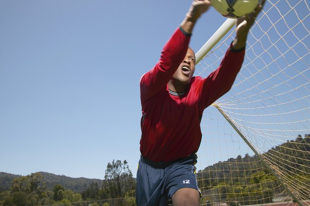 Young man holding a football near a goal post