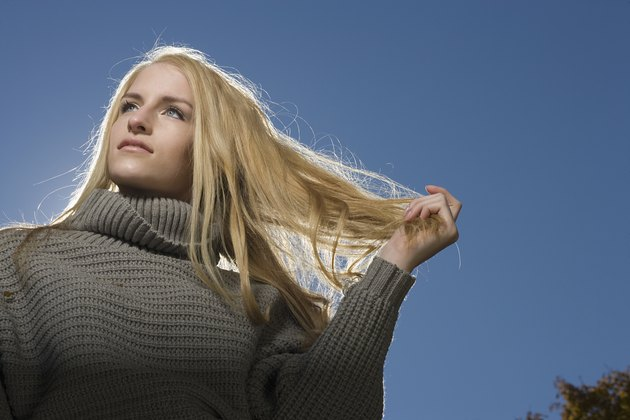 Portrait of carefree blonde woman outdoors running hand through hair