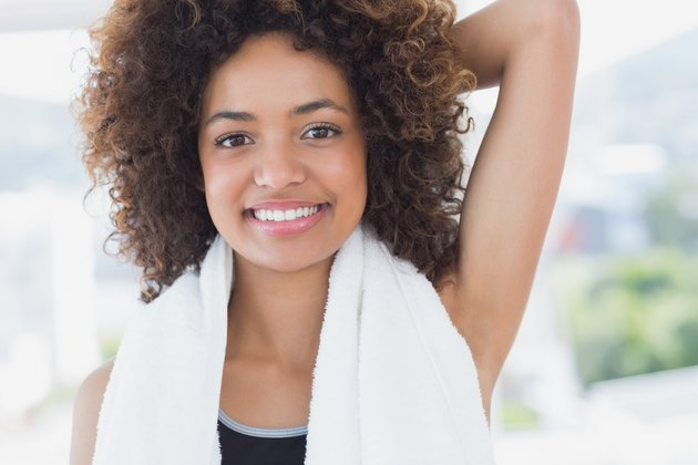 Sporty woman stretching hand behind back in fitness studio