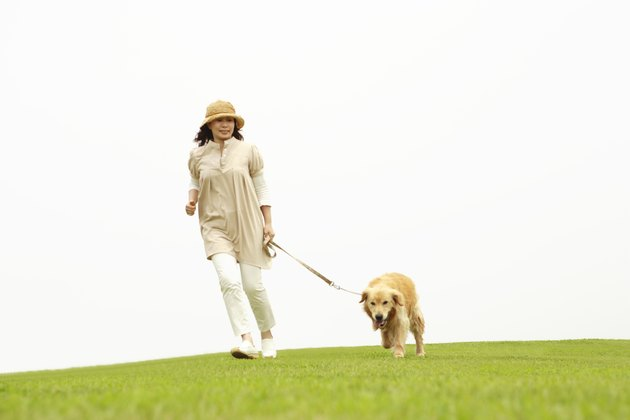 Mature woman running in a park with her dog
