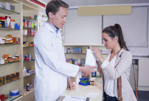 Pharmacist giving a bag of drugs to his sick client
