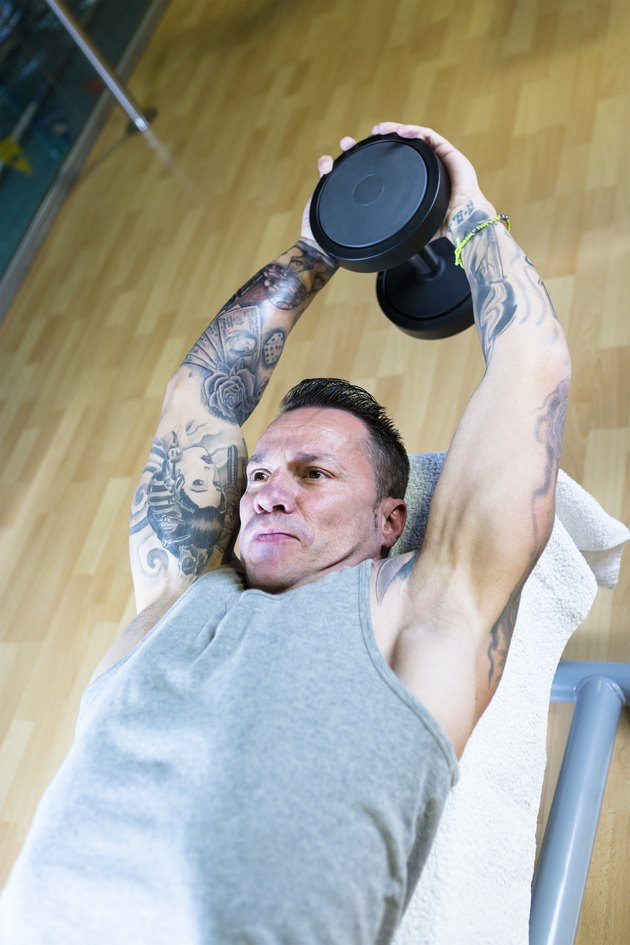 man making dumbbell pull overs - workout routine