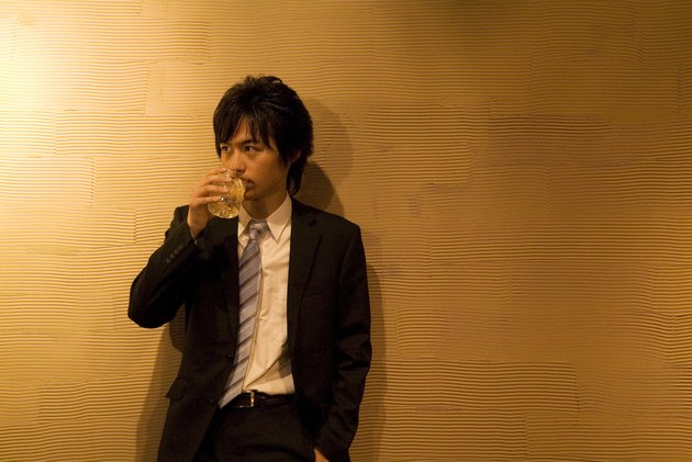 Businessman leaning against a wall with a drink