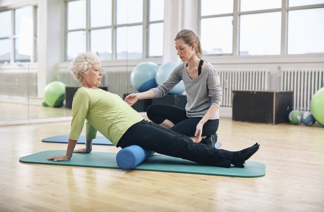 Old woman using foam roller with personal trainer