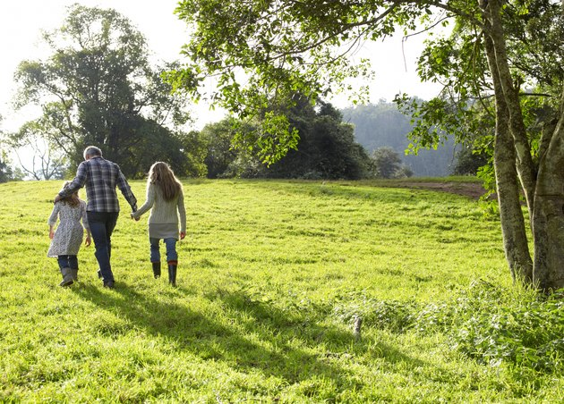 Family walking up a grassy hill together
