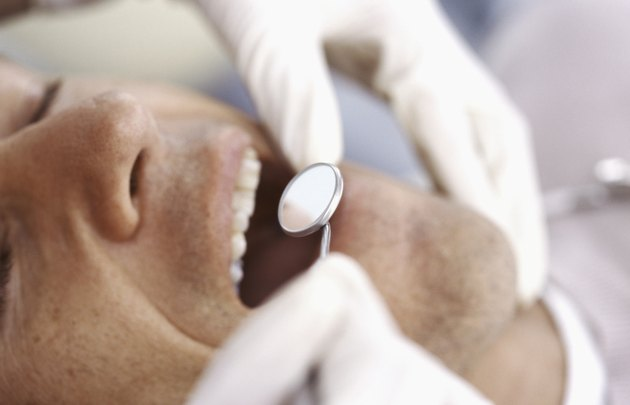 Dentist inspecting man's teeth with angled mirror, close-up