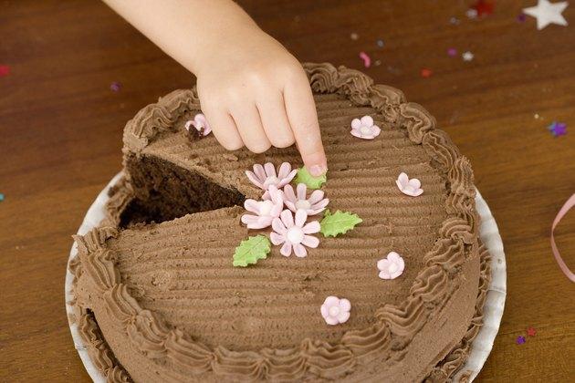 Hand touching cake