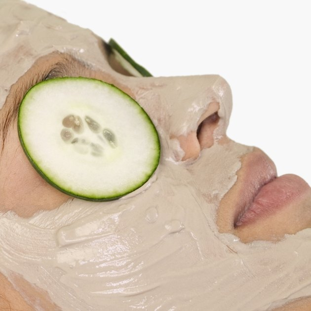 Young woman with mud mask and cucumber slices on eyes