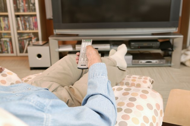 Man at television with remote control