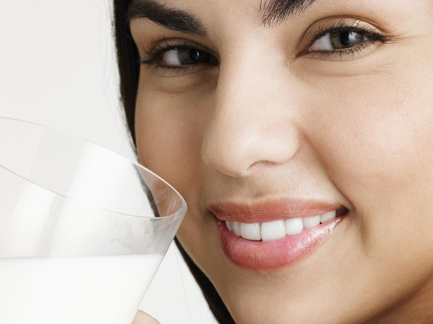 Young woman holding glass of milk, smiling, portrait, close-up of face