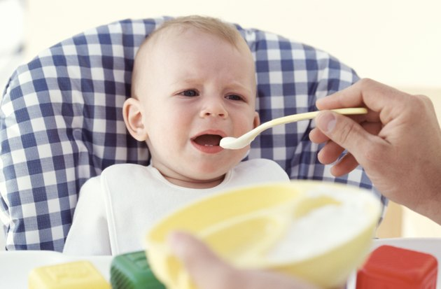 Father feeding baby (6-12 months), indoors