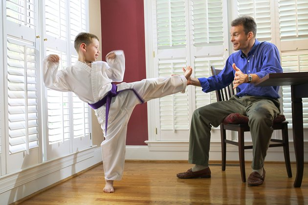 A boy in a martial arts uniform practices a side kick into his father's hand