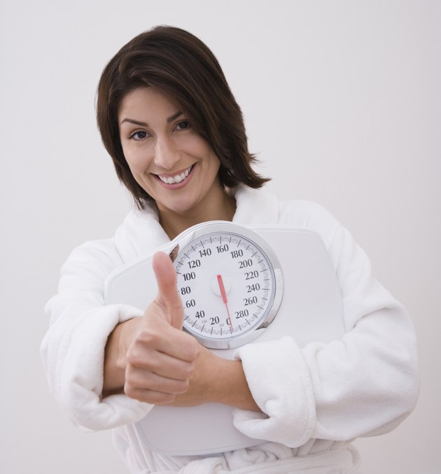 Hispanic woman holding scale and giving thumbs up