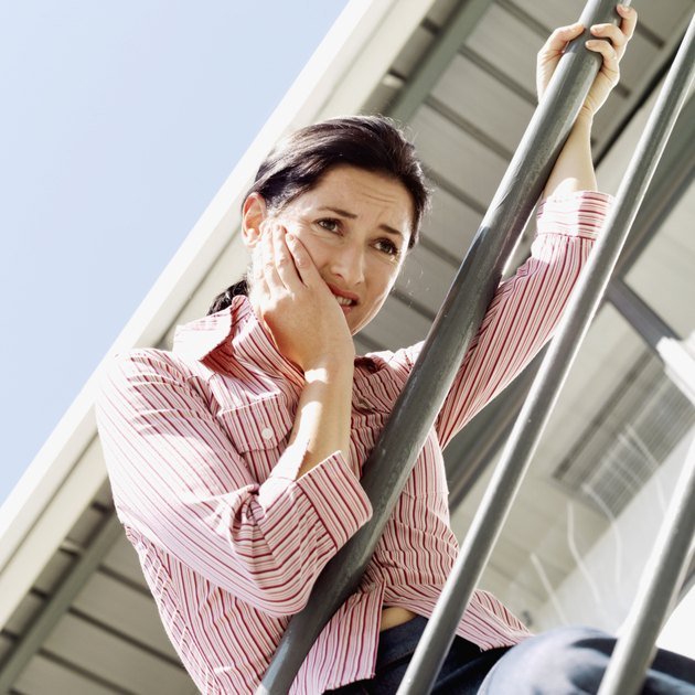 Low angle view of a woman leaning on a railing holding her cheek