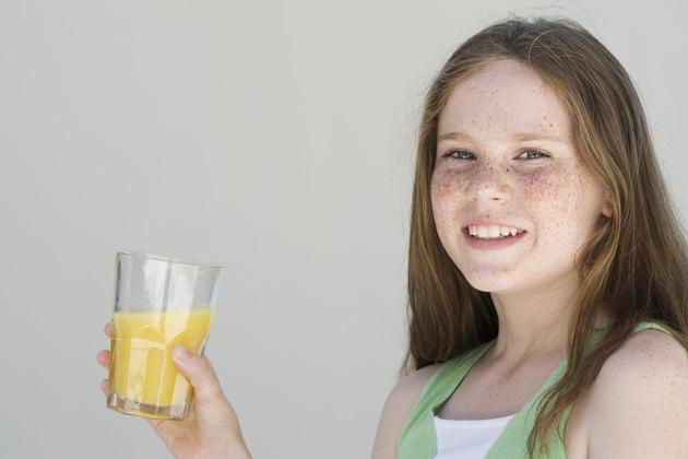 Girl holding glass of orange juice