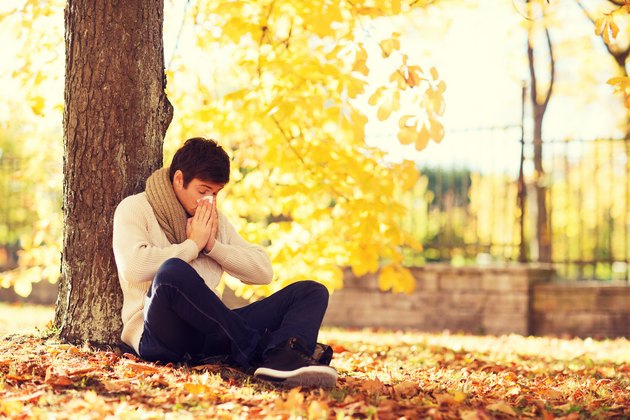 ill man with paper tissue in autumn park