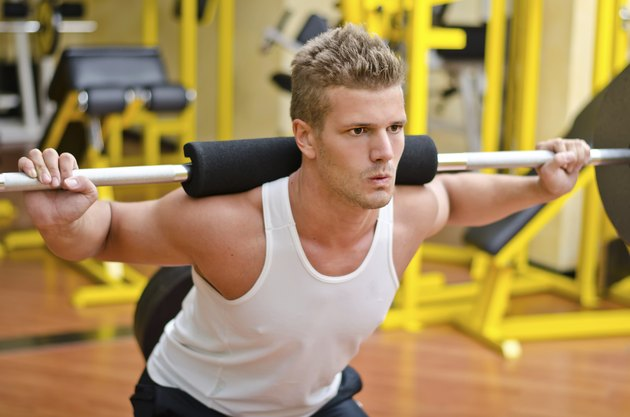 Handsome young man doing squats in gym