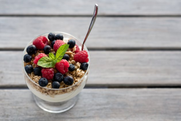 Cup of fresh fruits with cereals and yogurt.