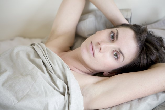 pensive brunette woman lying on bed