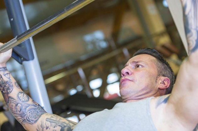 A muscular, tattooed man performs and incline barbell bench press at the gym.