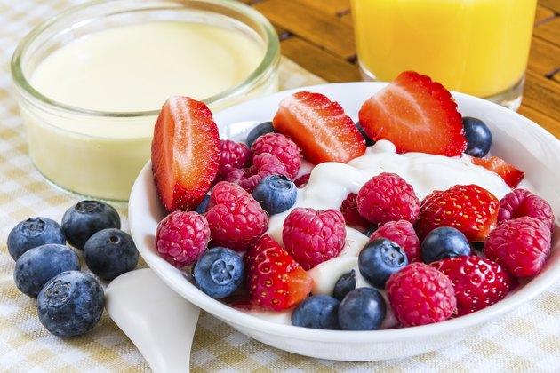 sweet raw berries with orange juice on coverlet