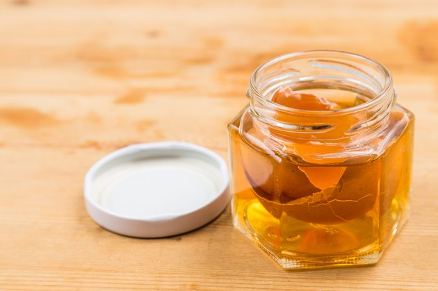 Jar containing soaked egg shell in apple cider vinegar