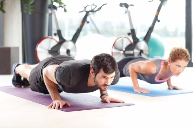 Portrait of personal trainer woman and man doing push ups at the gym.